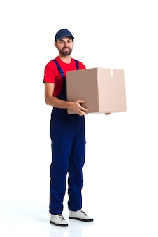Hard worker courier man holding a big box long view