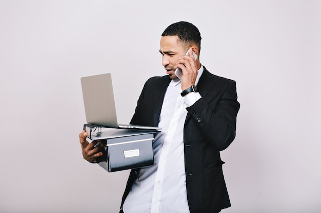 Hard-working astonished businessman with office box, folders, laptop talking on phone. office worker, career, smart manager, misunderstanding, leadership.