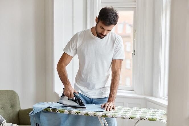 Hard working bearded man dressed in white t shirt