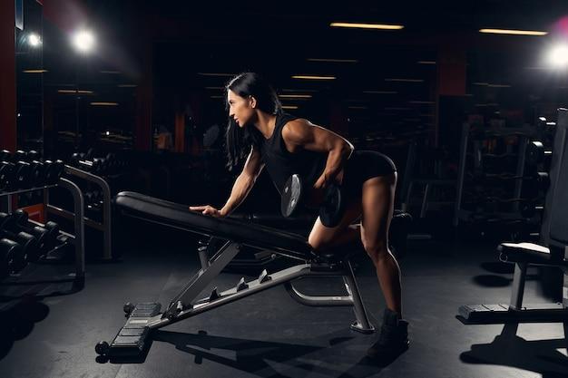 ジムで運動しながら、傾斜したベンチでウェイトを持ち上げる勤勉なフィットの女性