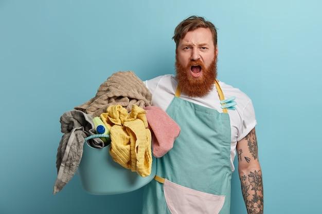 勤勉な生姜ひげを生やした男は、家事をし、洗濯で忙しく、洗濯かごを持って、エプロン、洗濯バサミを着て、大声で叫び、家事で過度に汚れています。家庭のコンセプト。