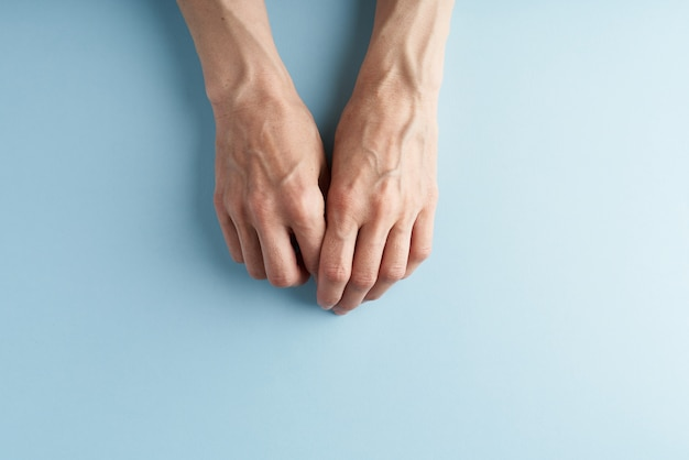 Hard-working hands with protruding veins on blue.