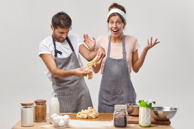 エプロンを着た勤勉な男性は、妻と一緒にベーキングスキルを練習し、ペストリーやパイの生地を作って、家で焼いて、テーブルの近くのキッチンで食材を使ってポーズをとります。おいしい夕食を準備する時間