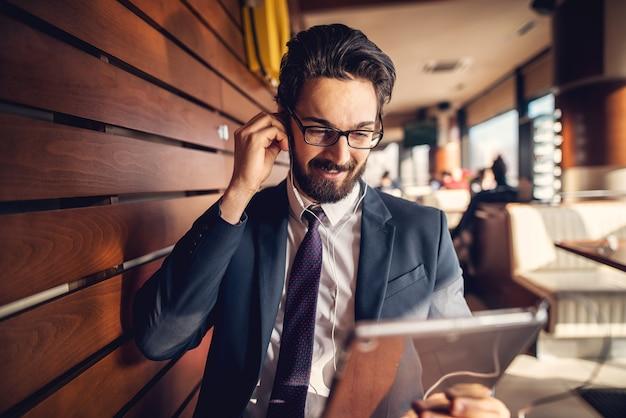 Трудолюбивая женщина среднего возраста красивая говоря по телефону и смотря компьютер в ее офисе.