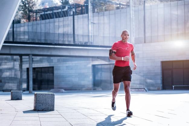勤勉なスポーツマン。競争の準備をしながら走っているハンサムなプロスポーツ選手