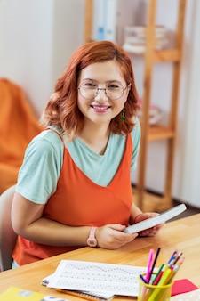 열심히 일하는 학생. 그녀의 집에서 작업을하는 동안 그녀의 매뉴얼을 들고 기쁘게 똑똑한 여자