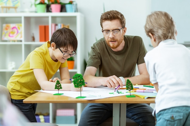 열심히 일하는 학생들. 사진을 가리키며 젊은 자연 애호가에게 의미를 설명하는 똑똑한 수염 선생님