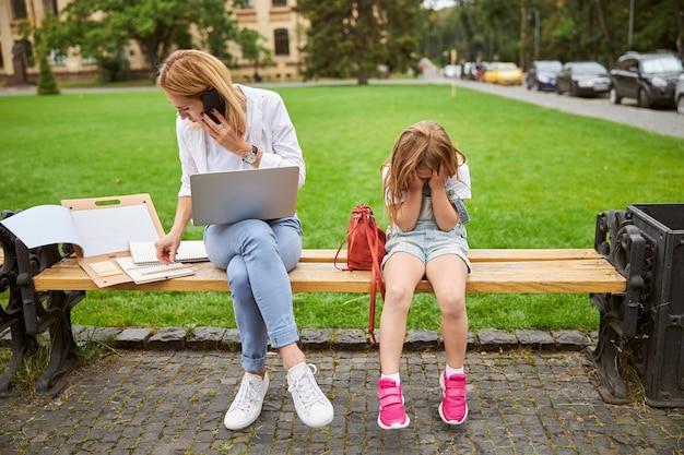 노트북 및 모바일과 그녀의 여성 자녀가 관심을 필요로하는 열심히 일하는 여성
