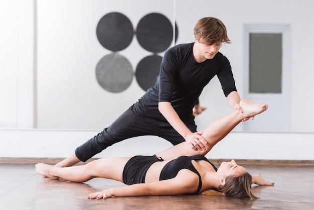 ハードワークアウト。彼女の足を持ち上げて、床に横たわっている間彼女のダンスパートナーを見ている格好良い美しい永続的な女性
