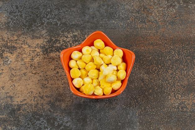 オレンジ色のボウルに固い黄色のキャンディー。