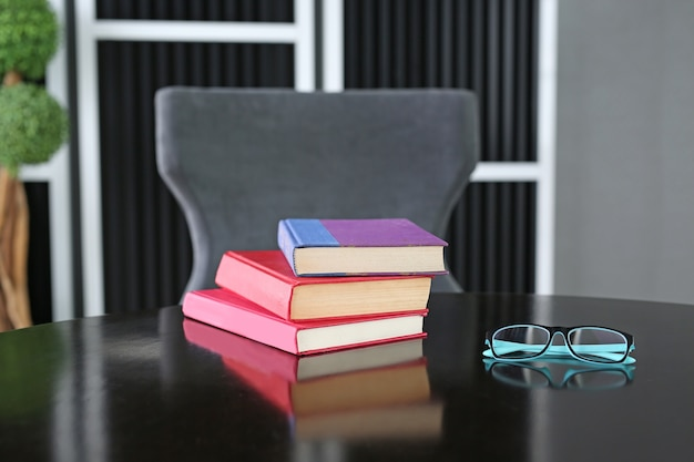 Hardback books on wooden table with glasses