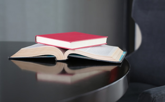 Hardcover book place on open book on wooden table.