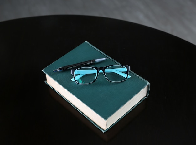Hardcover book with pen and glasses on wooden table.