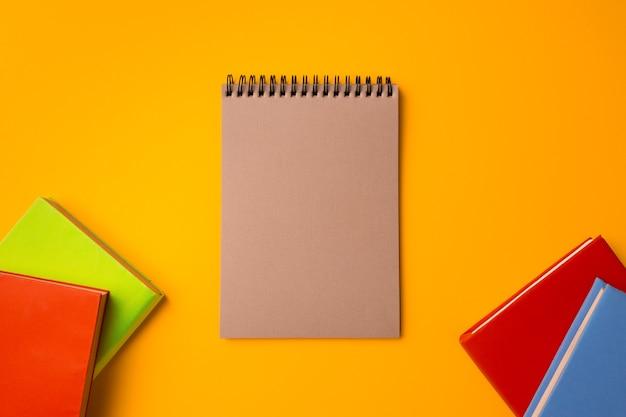 黄色の背景の平面図、コピー領域のハードカバーのメモ帳