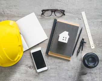 Hardhat and stationery near smartphone and cup