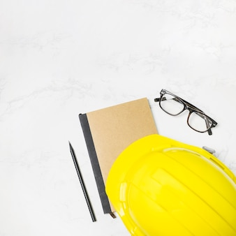 Hardhat and glasses near construction journal