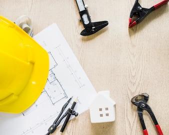 Hardhat near blueprint and construction tools