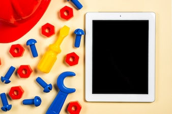 Hardhat; screws; bolts; spanner tool and screwdriver near the digital tablet with black screen on beige backdrop