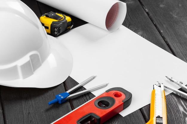 Закройте белый hardhat и различные инструменты для ремонта с копией пространства в середине