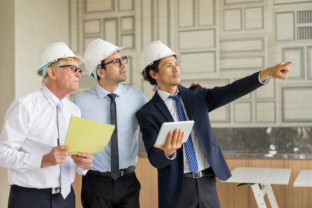 Три человека в галстуках и hardhats удивлены окном сцены.