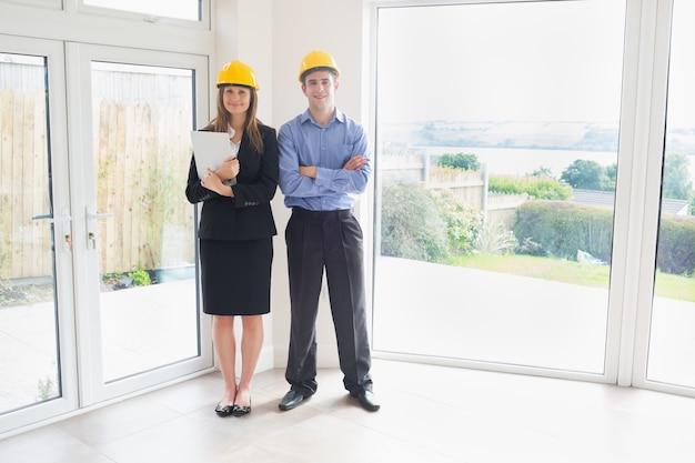 Агент по недвижимости и клиент, одетый в hardhats