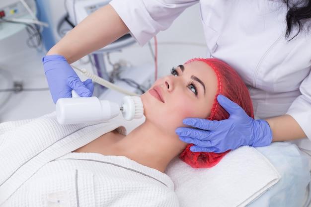 ハードウェア美容。美容師は、表面剥離の機械的手順を実行します。ブラシによる皮膚の洗浄。