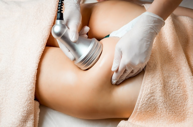 Hardware cosmetology. body care. spa treatment. ultrasound cavitation body contouring treatment. woman getting anti-cellulite and anti-fat therapy in beauty salon.