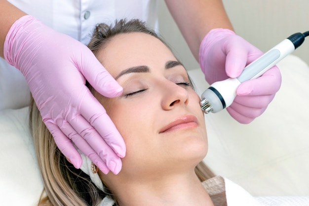 Hardware cosmetology. close up picture of lovely young woman with closed eyes receiving rf lifting procedure in beauty salon.