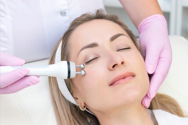 Аппаратная косметология. крупным планом изображение прекрасной молодой женщины с закрытыми глазами, получающих процедуру подъема rf в салоне красоты.