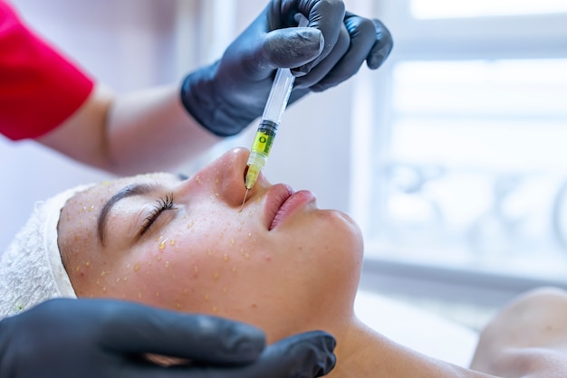 Hardware cosmetology, mesotherapy, portrait of young woman getting treatment of forehead zone