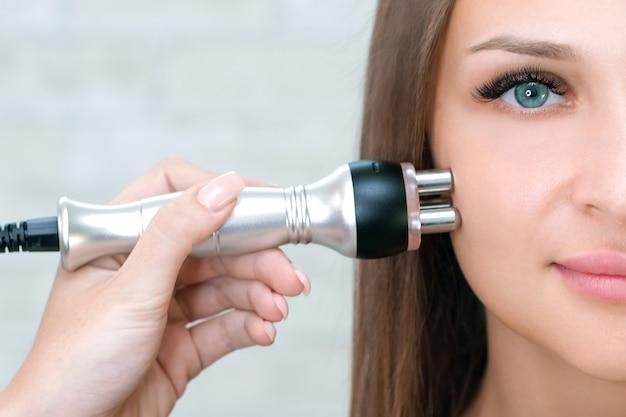 하드웨어 미용. 미용실에서 rf 안면거상술을 받는 젊은 여성.