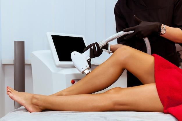 소녀의 몸에 하드웨어 제모 절차. 미용사는 미용실에서 다리의 레이저 제모를 합니다. 스킨 케어, 하드웨어 화장품.