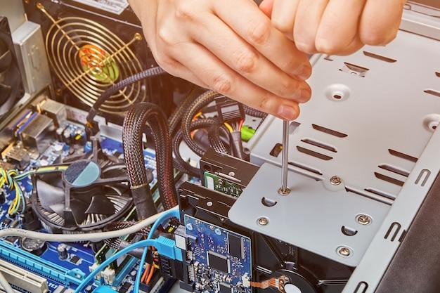 Аппаратный монтаж системного блока компьютера с помощью отвертки.