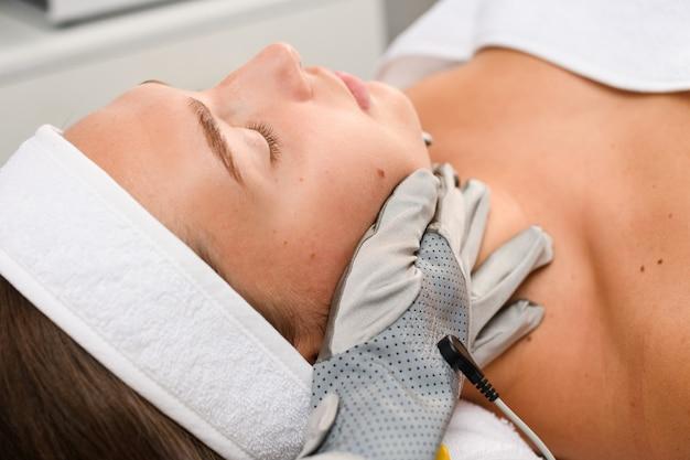 Аппаратный профессиональный косметолог трогает лицо клиента серыми микротоковыми перчатками