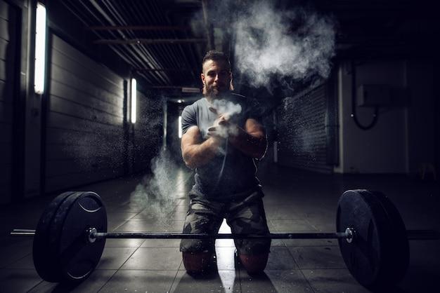 Трудолюбивый активный фитнес сильный мускулистый бородатый культурист человек приседает и хлопает в ладоши с меловым порошком перед силовой тренировкой с тяжелой гантелью.
