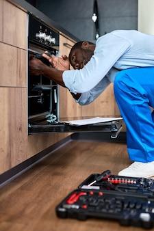 作業服を使用して、自宅のキッチンで壊れた電気オーブンを修理する青い作業服を着た勤勉なアフリカ系アメリカ人の男。側面図の肖像画。便利屋は修理プロセスに集中しています