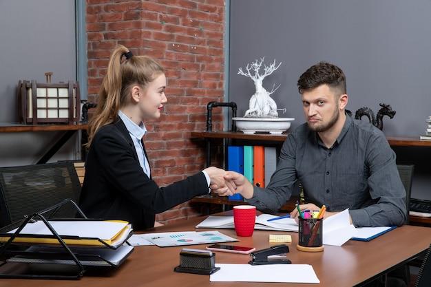 勤勉で集中して満足している専門家チームがオフィスの文書で1つの問題について話し合っています