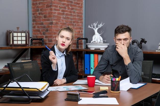 열심히 일하고 혼란스러운 관리 팀이 사무실의 문서에서 한 가지 문제를 논의하고 있습니다.