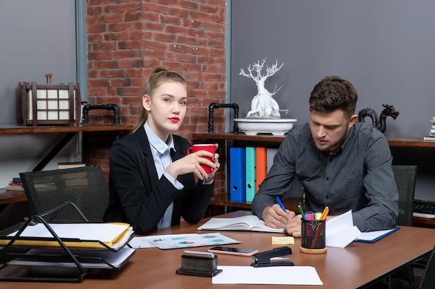 사무실에 있는 문서에서 한 가지 문제를 논의하는 근면하고 진지한 전문 노동자