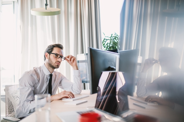 Hardworking caucasian employee in shirt and tie and with eyeglasses sitting in office and working on important project.