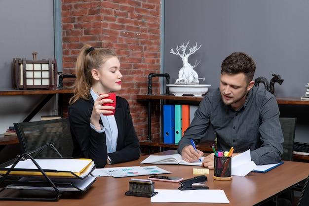Team di professionisti laboriosi e concentrati che discutono di un problema nei documenti in ufficio