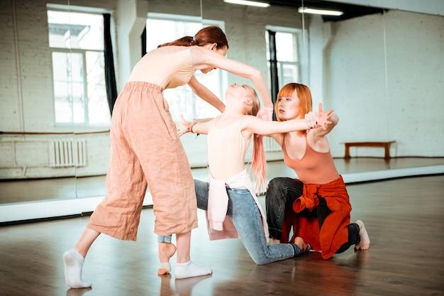 勤勉なダンサー。軽いスポーツウェアを着たダンススクールの2人の生徒と彼らの先生は集中しているように見えます
