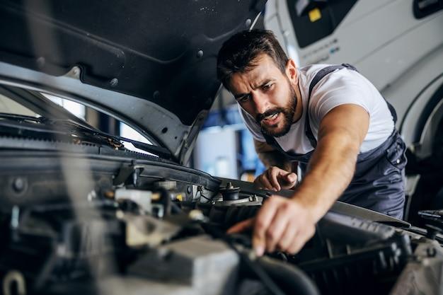 Hardworking dedicated bearded employee in overalls fixing car