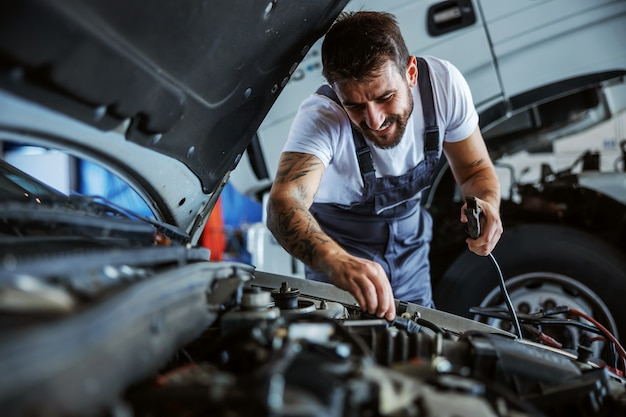 Hardworking dedicated bearded employee in overalls fixing motor. in background is truck. manual jobs concept.