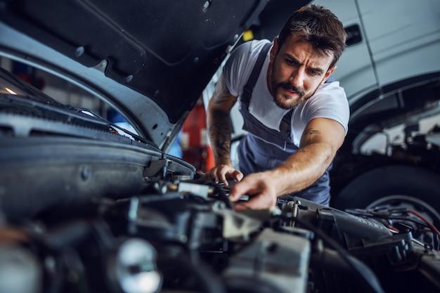 Hardworking dedicated bearded employee in overalls fixing motor. in background is truck