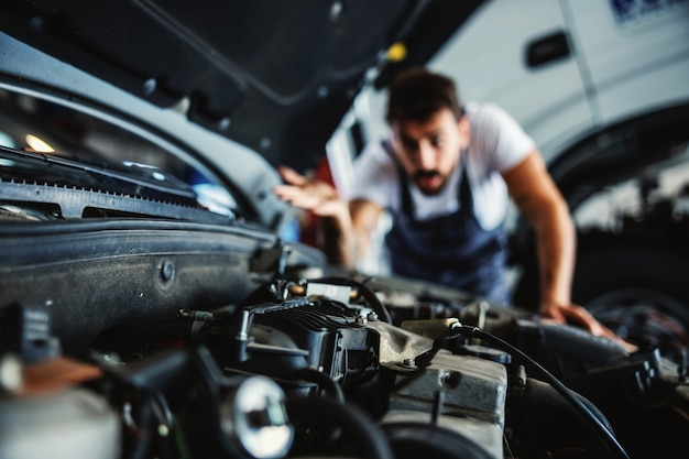 Hardworking dedicated bearded employee in overalls fixing motor. he have no idea what is wrong.