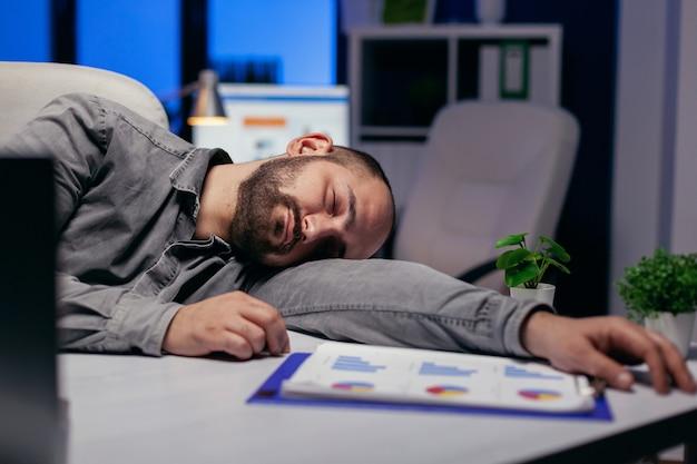 열심히 일하는 기업가는 마감일 때문에 직장에서 테이블에서 잔다. 워커홀릭 직원은 중요한 회사 프로젝트를 위해 사무실에서 밤늦게 혼자 일하다 잠들었습니다.