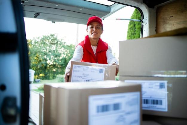 Трудолюбивая женщина-курьер готовит посылки перед доставкой.