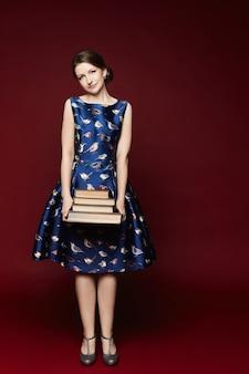 파란 드레스를 입고 책을 손에 들고 아름다운 카메라를 바라보는 열심히 일하는 여학생 ...