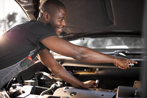 Hardworking guy employee in uniform works in the automobile salon